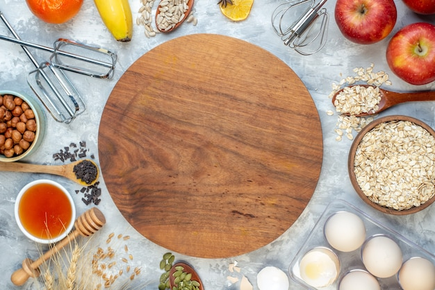 Top view brown wooden desk with apples bananas eggs raw cereals and seeds on a white background dough pie seed milk fruit color corn cook cake