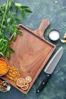 ダークブルーの表面に大きなナイフが付いた上面図茶色の木製デスク古代料理食用色素肉屋キッチンナイフ