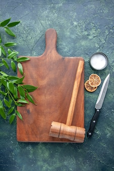 Top view brown wooden desk with hammer on the dark-blue surface color wood kitchen sharp brown cutlery tree spoon