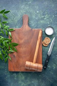 ダークブルーの表面色の木製キッチンシャープブラウンカトラリーツリースプーンにハンマーで上面図茶色の木製デスク