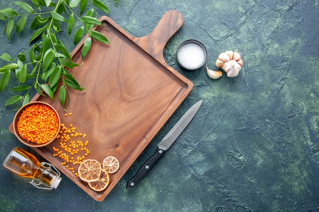 Top view brown wooden desk with orange lentils on dark blue background ancient cuisine color meat butcher kitchen knife food