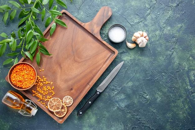 ダークブルーの背景にオレンジ色のレンズ豆が付いている上面図茶色の木製の机古代料理色肉肉屋包丁食品