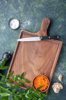 ダークブルーの表面にオレンジ色のレンズ豆が付いた上面図茶色の木製デスク古代料理色肉肉屋包丁食品