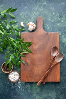 Top view brown wooden desk with spoons and seasonings on the dark-blue background color wood kitchen sharp cutlery tree spoon