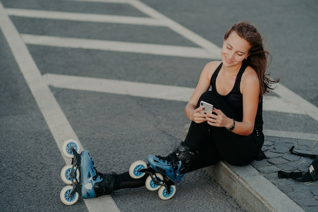 Top view of brunette active young woman uses smartphone for online communication poses on asphalt dressed in black active wear enjoys favorite hobby and free time. extreme sport and rest concept