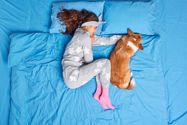 Top view of brunette young european woman in pajama sleeps together with favorite pet sees sweet dreams feels comfortable has healthy slumber poses on bed. people relaxation animals bedtime concept