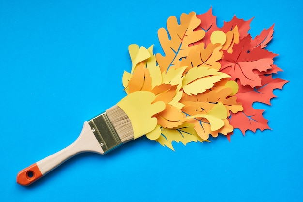 Top view of brush loaded with autumn leaves on blue paper