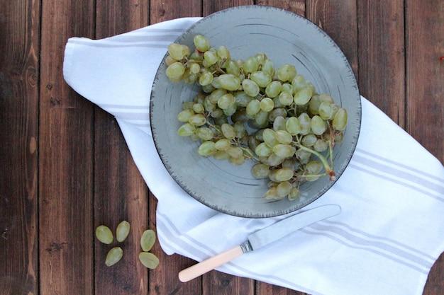 Вид сверху кисть зеленого винограда в чашке с ножом на столе