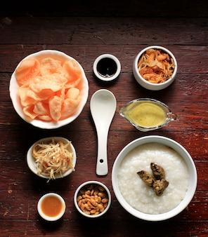 상위 뷰 bubur ayam(인도네시아 치킨 죽), 음식 놀링 구성이 나무 배경에 있습니다. 부부르 아얌 반둥 성분