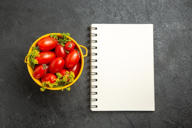 Top view bucket of cherry tomatoes and dill flowers and a notebook on dark background