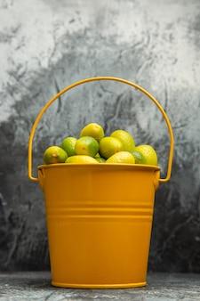 Vista dall'alto di un secchio pieno di mandarini verdi freschi su sfondo grigio