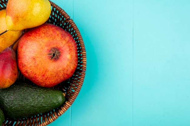 Top view of a bucket full of pomegranate with mango avocado on blue with copy space