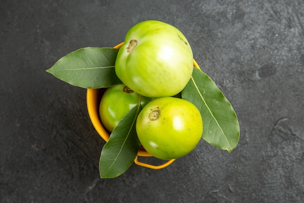 Top view bucket of green tomatoes and bay leaves on dark background