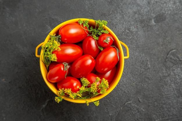 어두운 배경에 체리 토마토와 딜 꽃의 상위 뷰 양동이