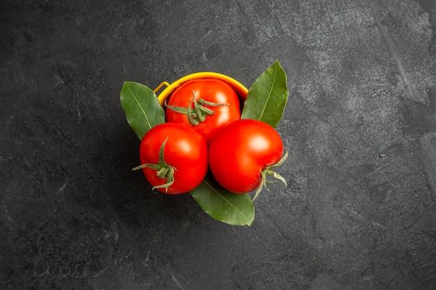 Vista dall'alto un secchio con pomodori e foglie di alloro su fondo scuro