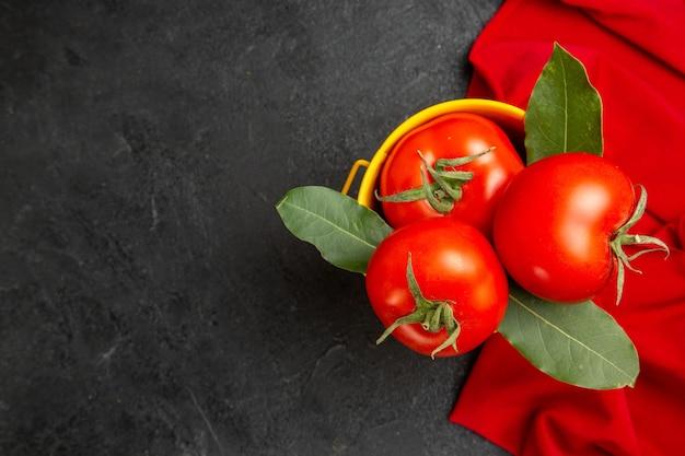 Vista dall'alto un secchio con pomodori e foglie di alloro sull'asciugamano rosso su fondo scuro