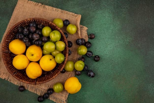 Vista dall'alto di un secchio di pesche gialle con prugne ciliegia verdi con prugnole su un panno di sacco su uno sfondo verde con spazio di copia