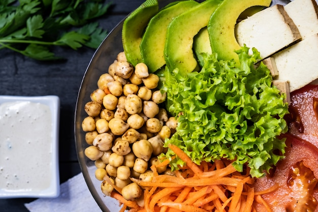 Top view of buddha bowl on a rustic table. vegan meal of chickpeas, salad, vegetables, tofu and avocado, flat lay