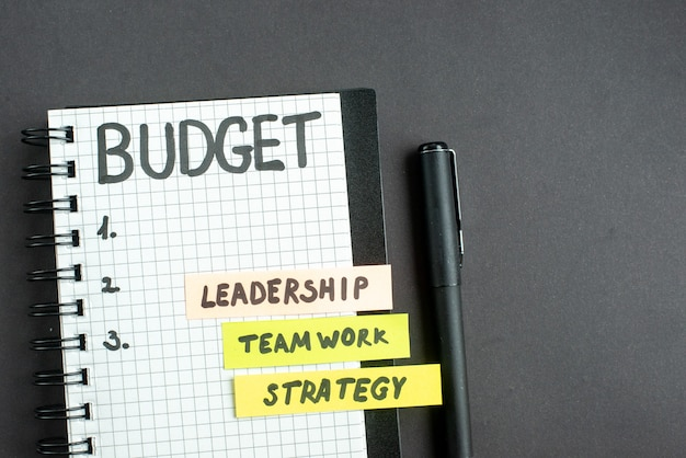 暗い表面戦略ビジネスマーケティングチームワークオフィスリーダーシップ仕事の成功にペンでメモ帳のトップビュー予算メモ