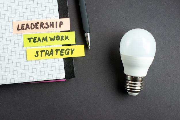 Vista dall'alto nota di bilancio nel blocco note con la penna sulla superficie scura lavoro di marketing aziendale lavoro di squadra leadership lavoro successo