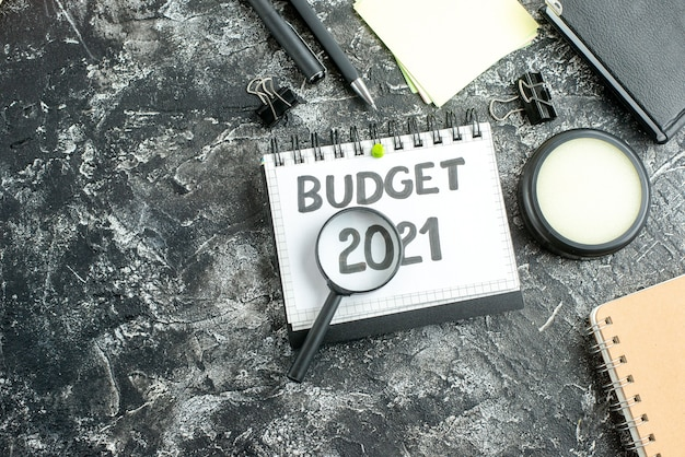 Top view budget note with magnifier on dark surface color college student school job bank business