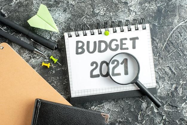 暗い表面の色の大学生の学校のお金のビジネスの仕事の仕事にペンと拡大鏡を備えた上面図の予算ノート