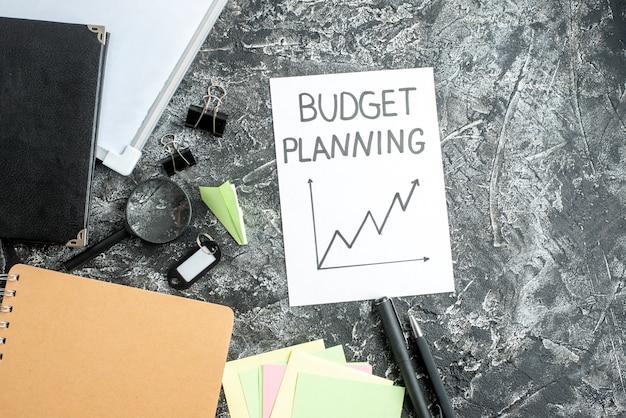 灰色の表面のペンでトップビュー予算計画ノート仕事コピーブック学校学生ビジネス仕事大学のお金の予算