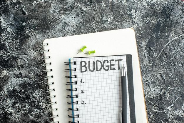 Vista dall'alto bilancio nota scritta sul blocco note con la penna sulla superficie scura studente quaderno di colore scuola grigio college business