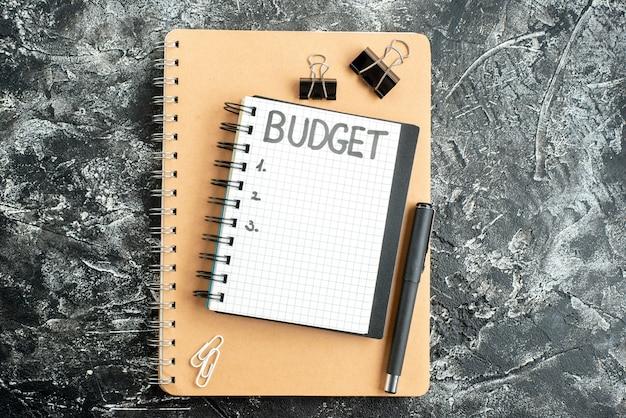 Vista dall'alto bilancio nota scritta sul blocco note con la penna sulla superficie scura studente colore quaderno scuola denaro grigio business
