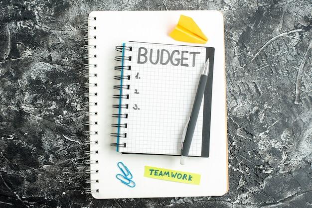 Vista dall'alto bilancio nota scritta sul blocco note con penna su sfondo grigio studente colore quaderno scuola college scuro affari soldi lezioni