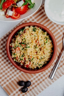 Top view of bulgur with tomatoes on the table