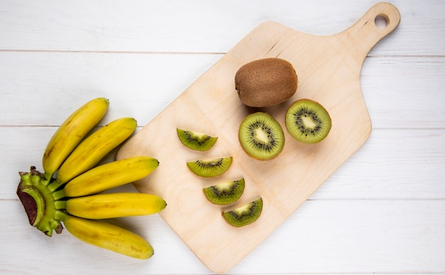 Top view of bunch of banana with slices of kiwi fruit on wooden cutting board on white rustic