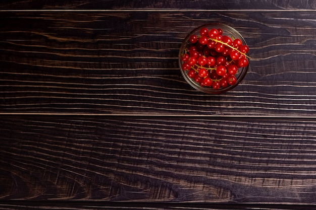 Top view of a bunch of cherry tomatoes in a glass bowl on a wooden table