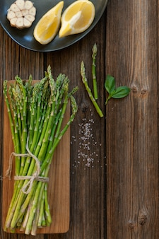 Top view of bunch of fresh green asparagus with lemon and garlic on wooden table