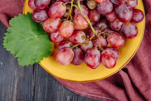 Top view of a bunch of fresh sweet grapes in a plate with green leaf on rustic table