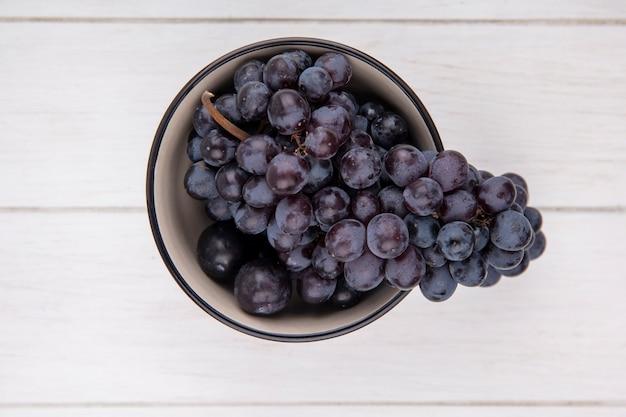Вид сверху гроздь черного винограда в миске на белом фоне
