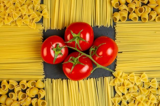 パスタとスパゲッティが装飾の形をしたトマトのトップビュー束