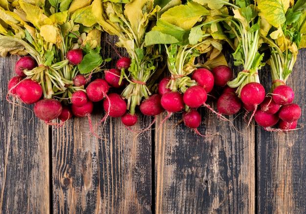 Mazzo di vista superiore di ravanelli freschi rossi con le foglie fresche sulla tavola di legno