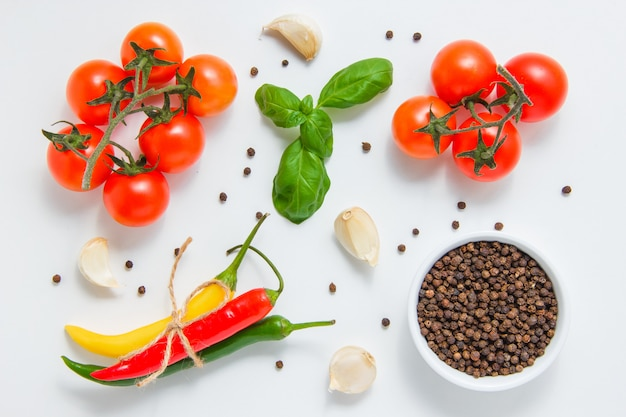 Top view bunches of tomatoes with a bowl of black pepper, garlic, leaves, chili pepper on white background. horizontal