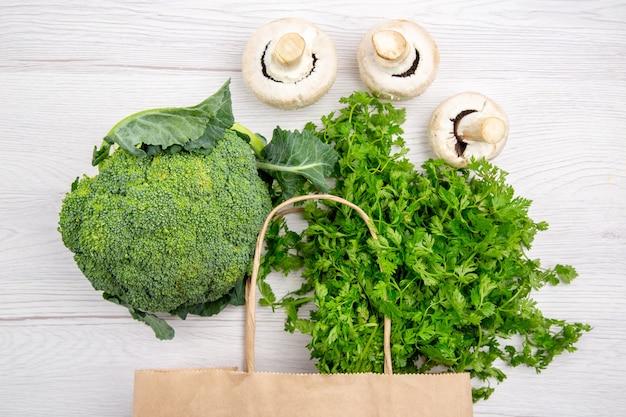 Vista dall'alto di un fascio di broccoli di funghi verdi freschi in un cesto su sfondo bianco