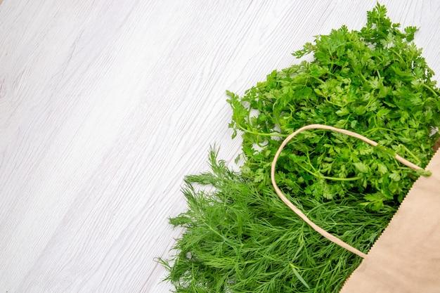 Vista dall'alto di un fascio di cipolla verde in un cesto sul lato sinistro su sfondo bianco