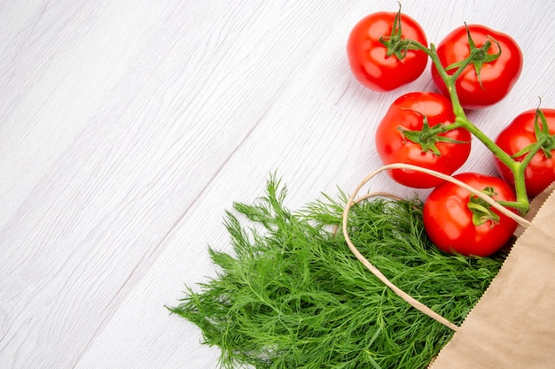 Top view of a bundle of green onion in a basket and tomatoes with stem on the left side on white background