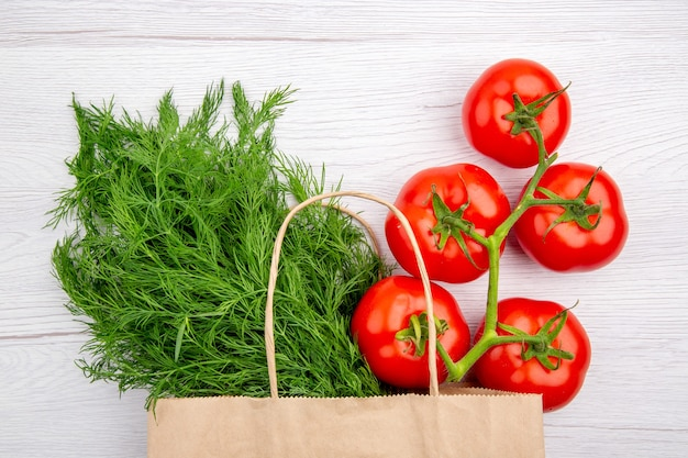 Top view of a bundle of green onion in a basket and tomatoes with stem on white background
