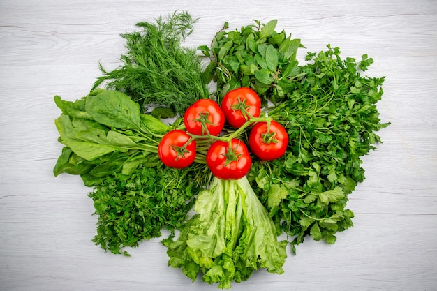 Top view of bundles of fresh greens and tomatoes with stem on white background