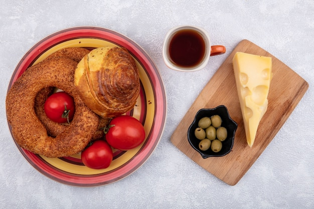 Top view of buns on a plate with fresh tomatoes with olives on a black bowl and cheese on a wooden cutting board on a white background