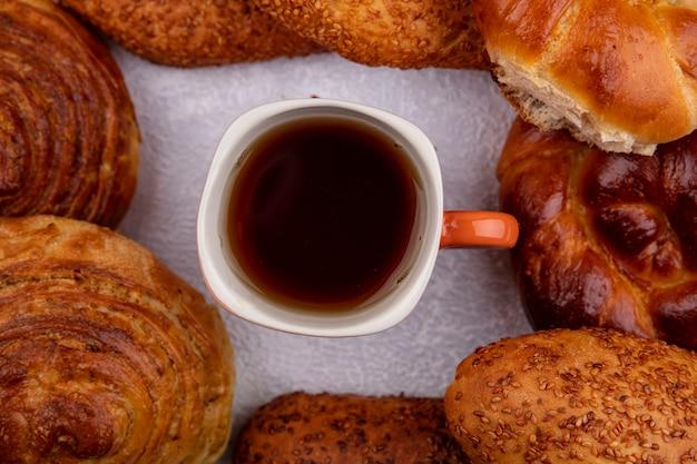 Vista dall'alto di panini come polpette di sesamo gogal con una tazza di tè su uno sfondo bianco