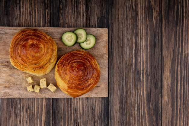 Top view of buns on a wooden kitchen board with chopped slices of cucumber and cheese on a wooden background with copy space