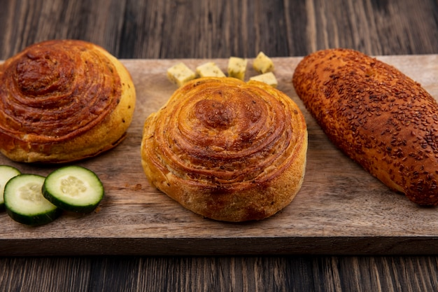 Top view of buns on a wooden kitchen board with chopped slices of cucumber and cheese on a wooden background