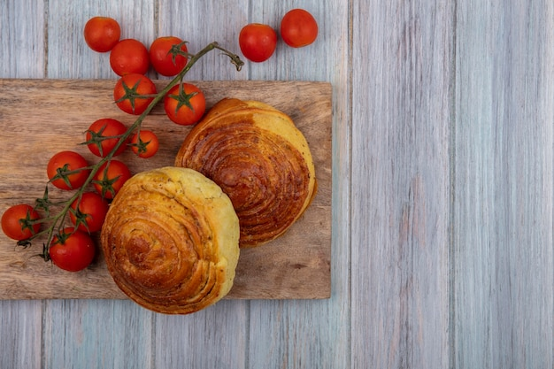 Top view of buns on a wooden kitchen board with fresh vine tomatoes on a grey wooden background with copy space