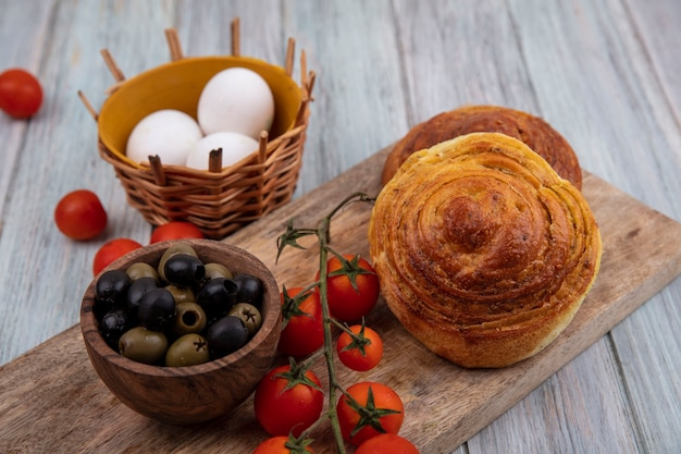 Top view of buns on a wooden kitchen board with fresh vine tomatoes with olives on a wooden bowl and eggs on a bucket on a grey wooden background